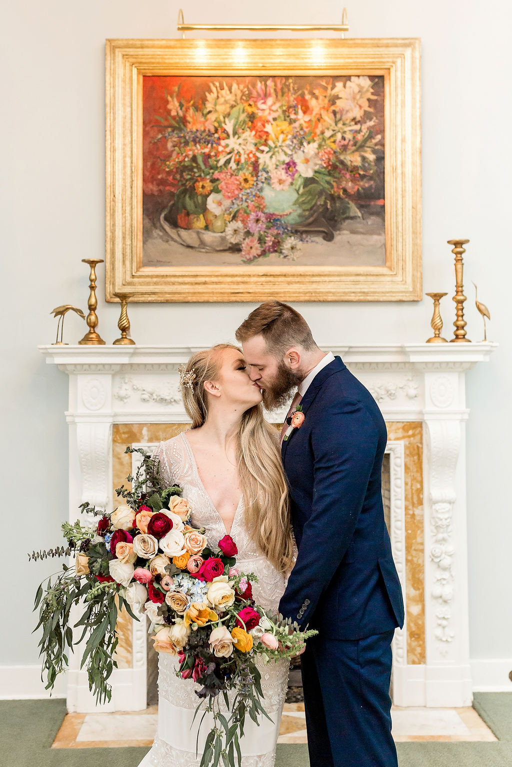 bride and groom kissing in front of a baroque fireplace