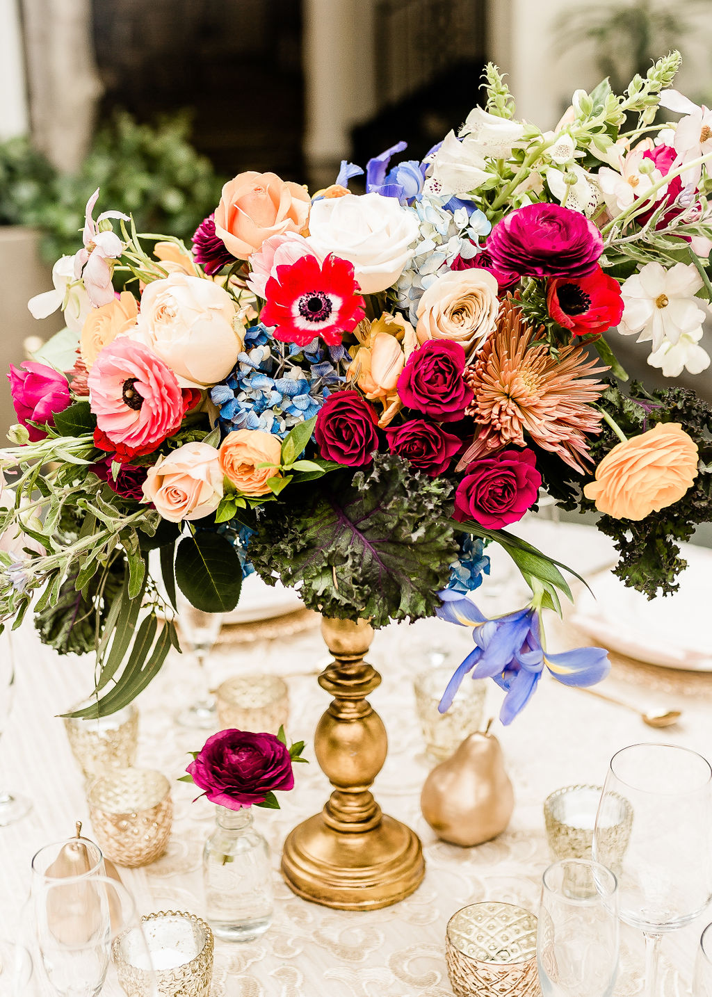 colorful floral centerpiece on a gold pedestal