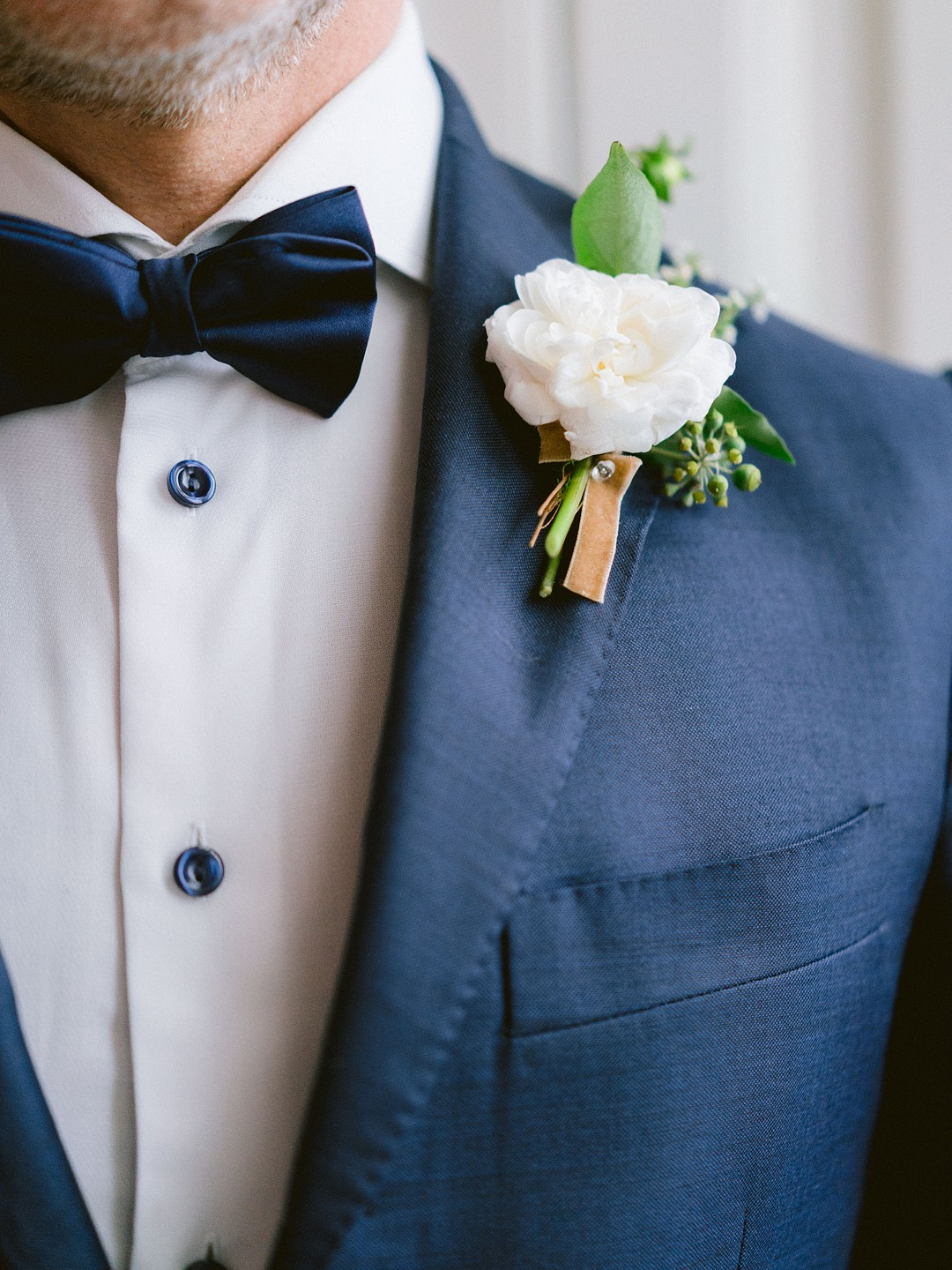 groom in a navy blue tux with a whit boutonniere