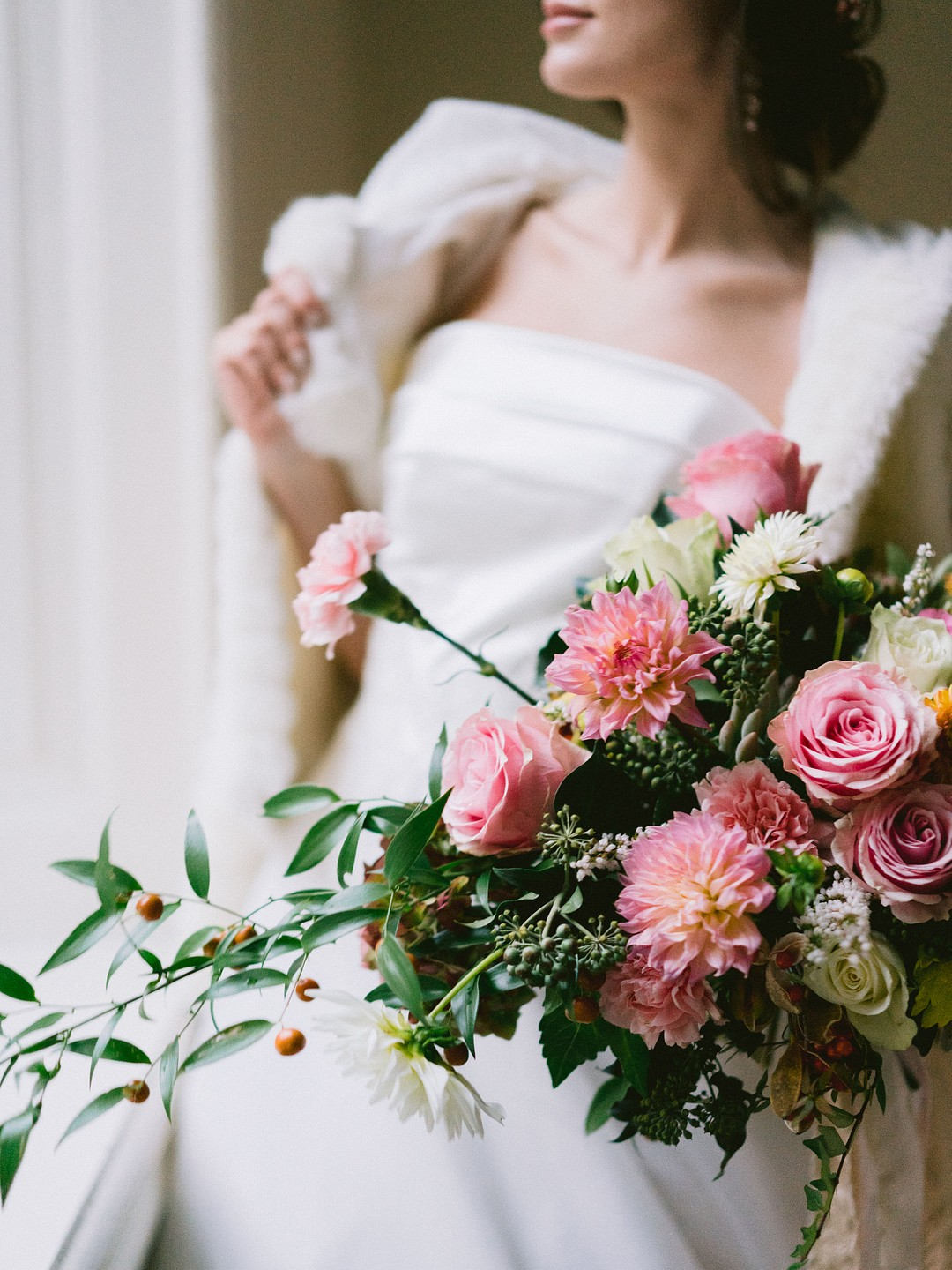 fine art bride hold ing a bouquet of pink flowers