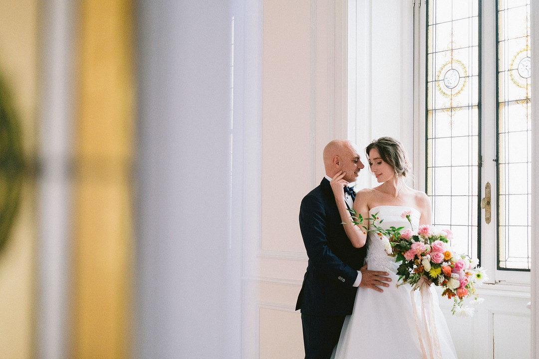 bride and groom photo in front of a large villa window
