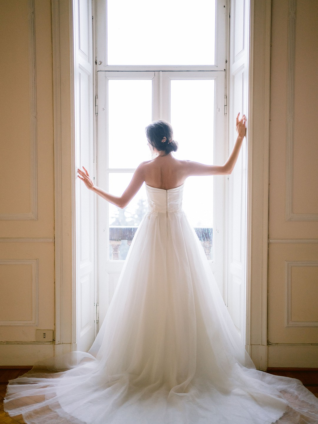 bride looking out the window as she gets ready