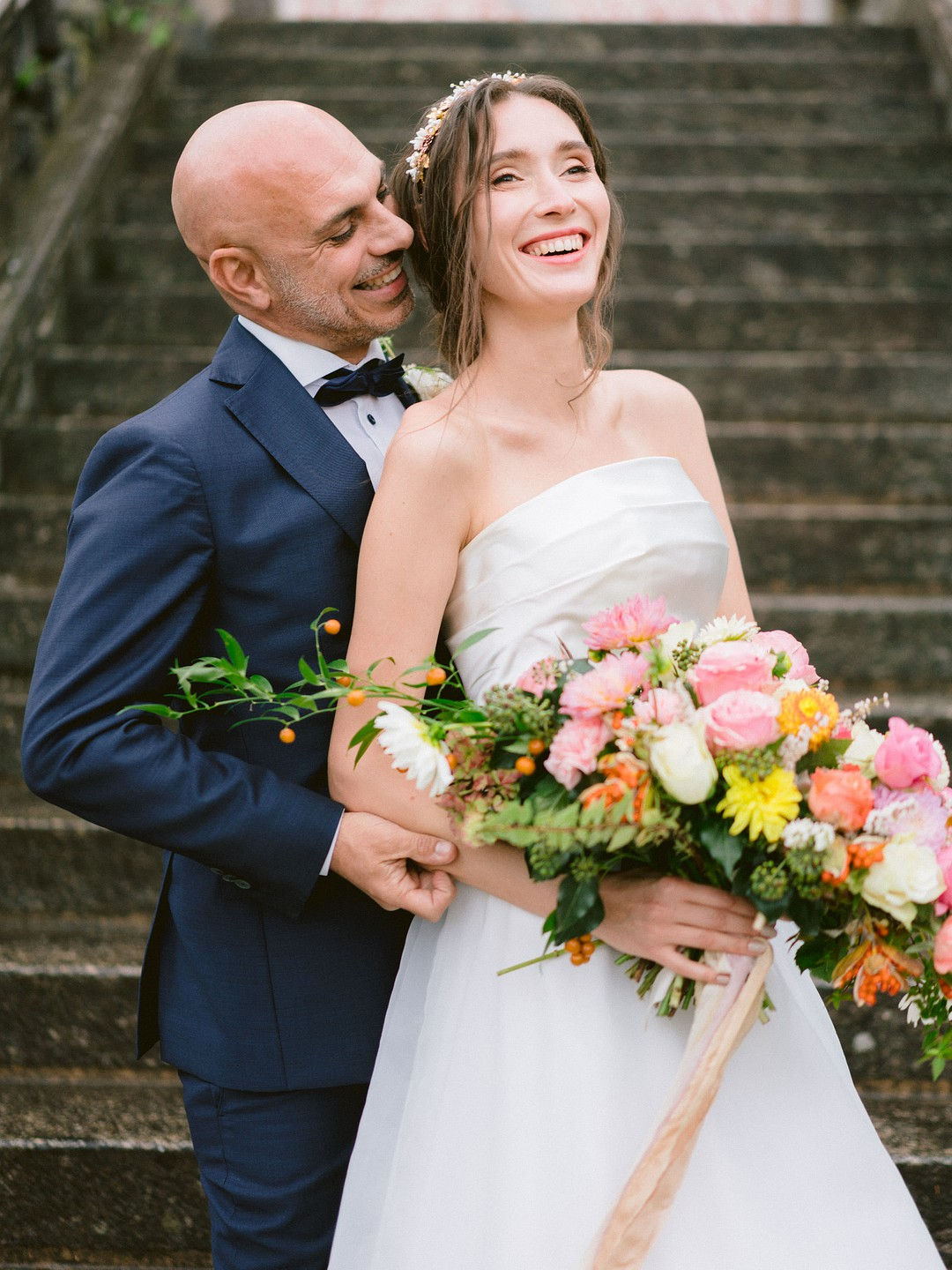 bride and groom smiling at the base of the villa staircase
