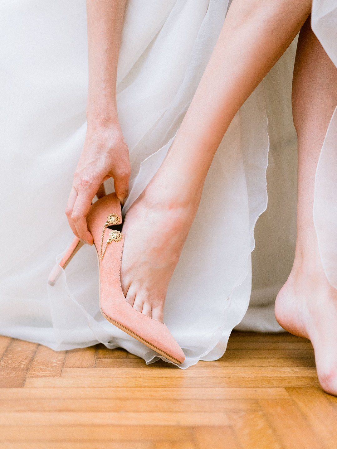 bride putting on pink suede weddings shoes