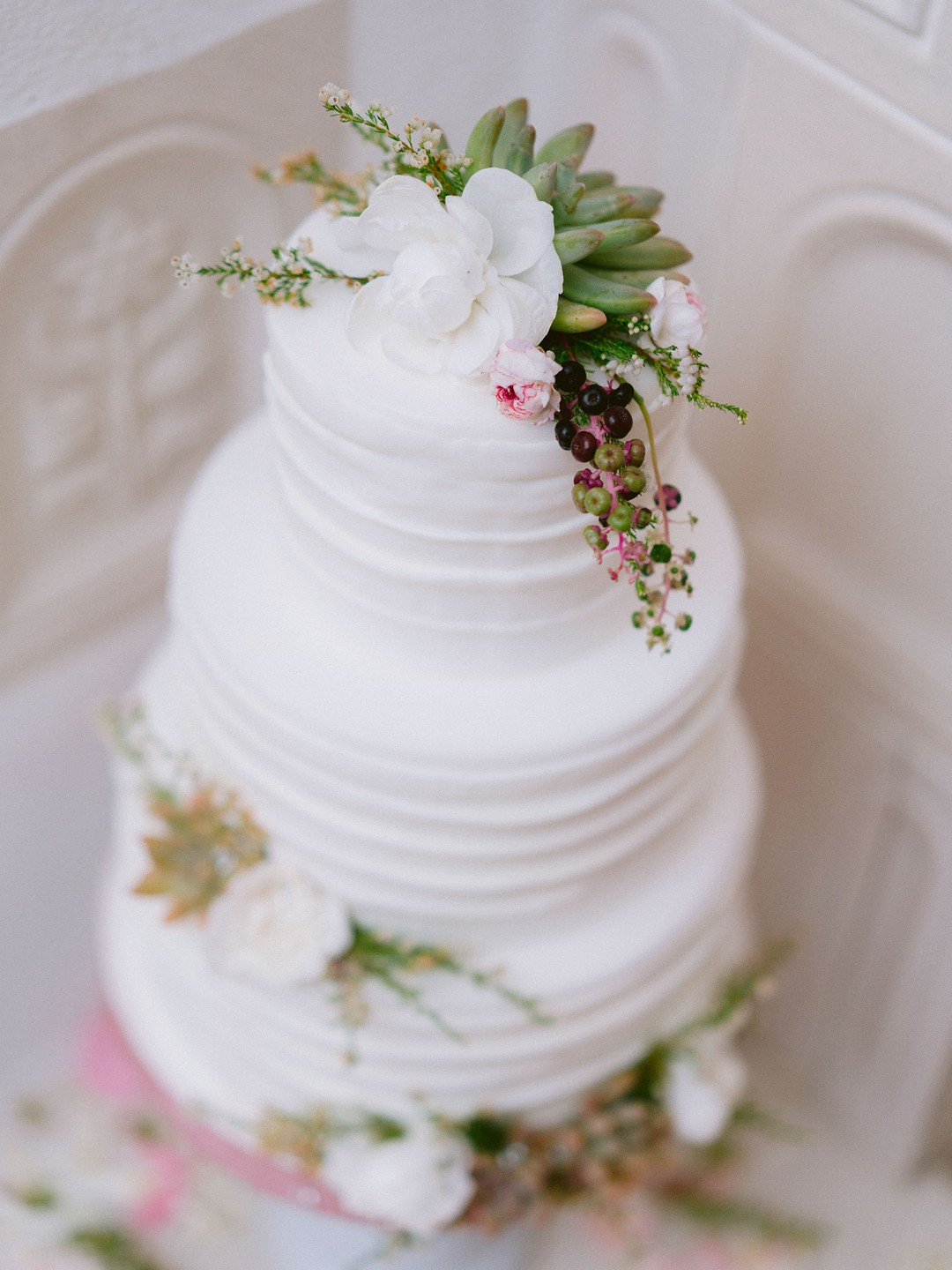 white cake covered with simple flowers