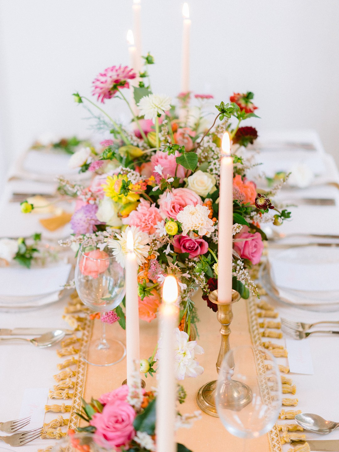 table decorated with a runner, colorful flowers and taper candles