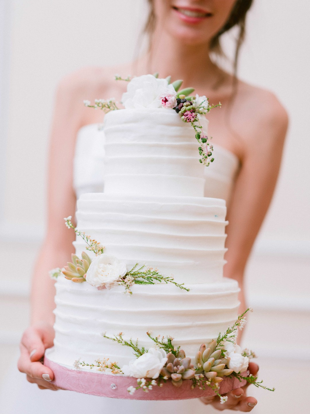 bride holding a simple three tier cake