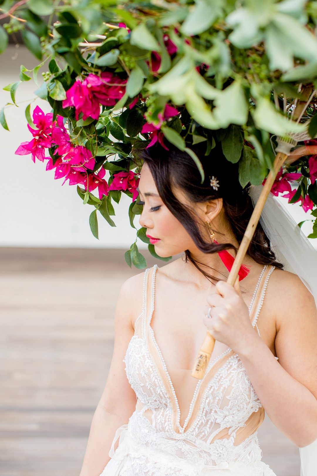 bride holding an umbrella covered in flowers