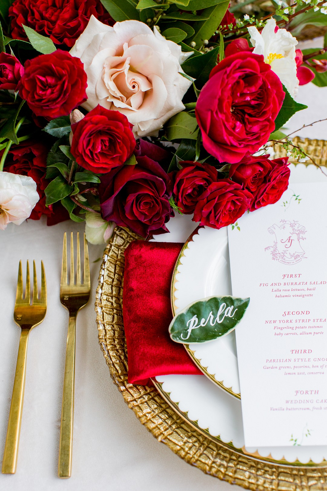 wedding place setting with a deep red napkin and red velvety roses