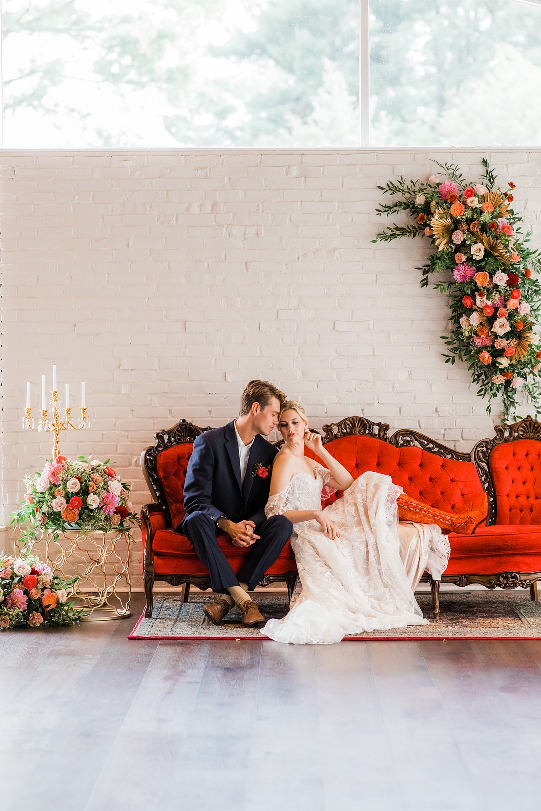 bride and groom sitting on a red couch