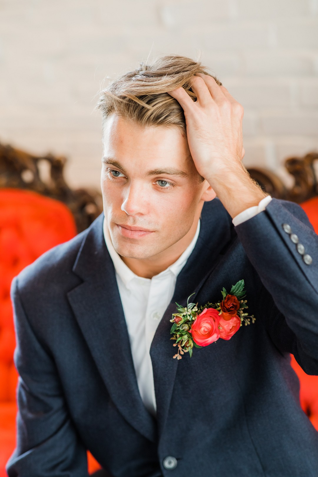 groom with a red boutonniere