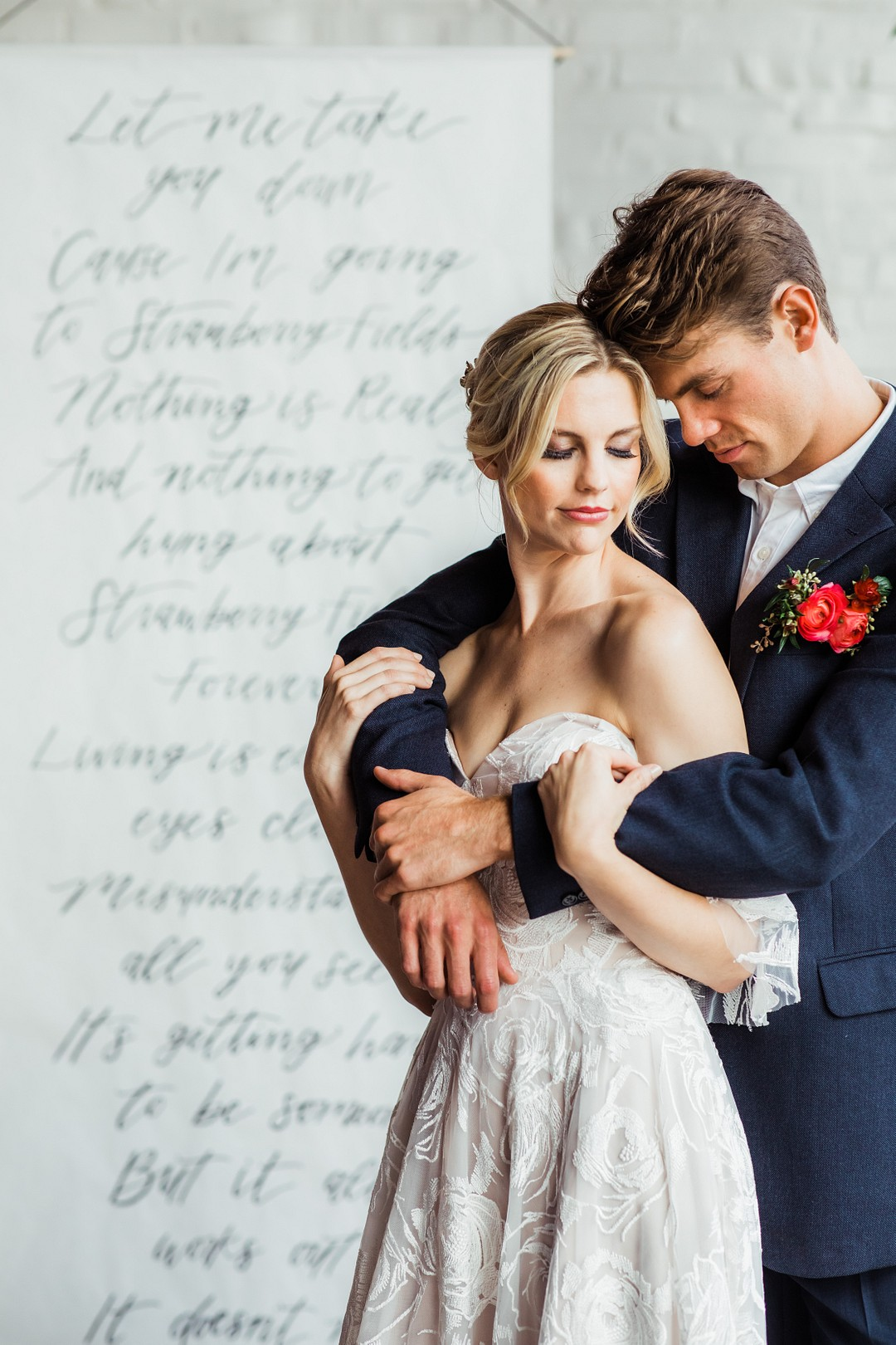 newlywed couple standing in front of a handwritten backdrop