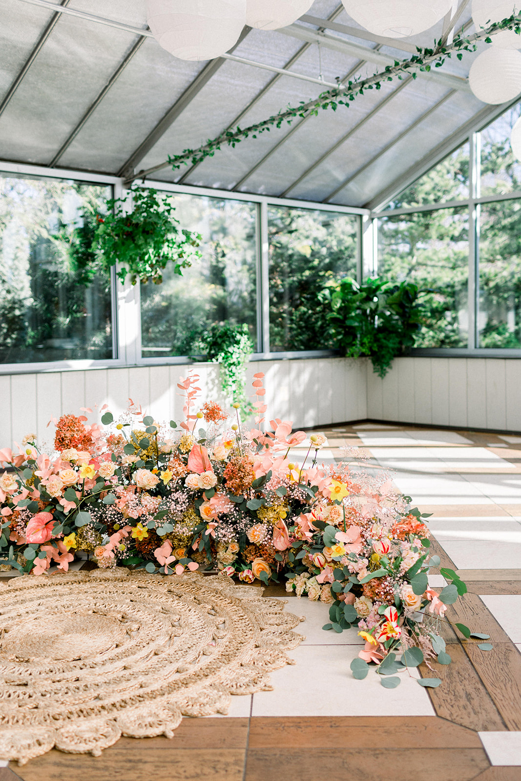 A half-circle of thick, lush florals, filled with everything from Anthurium, Garden Roses, Craspedia, and Ranunculus, created this unique shape floating above the ground.