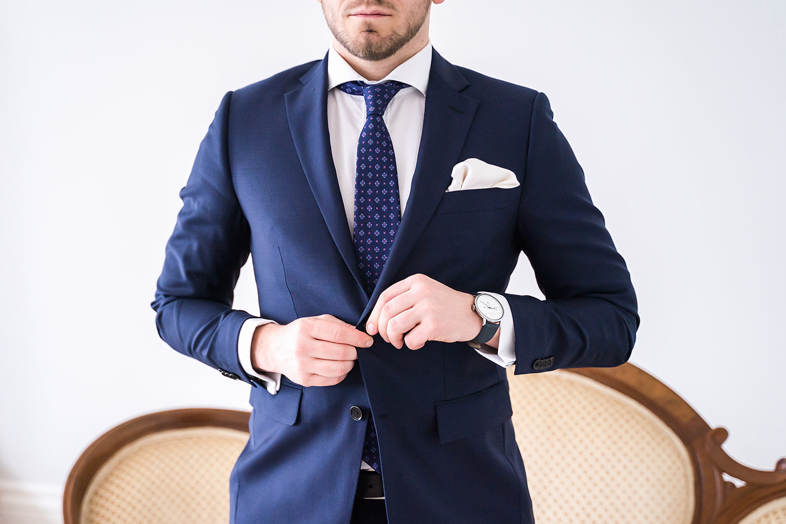 groom in a navy blue suite buttoning his jacket