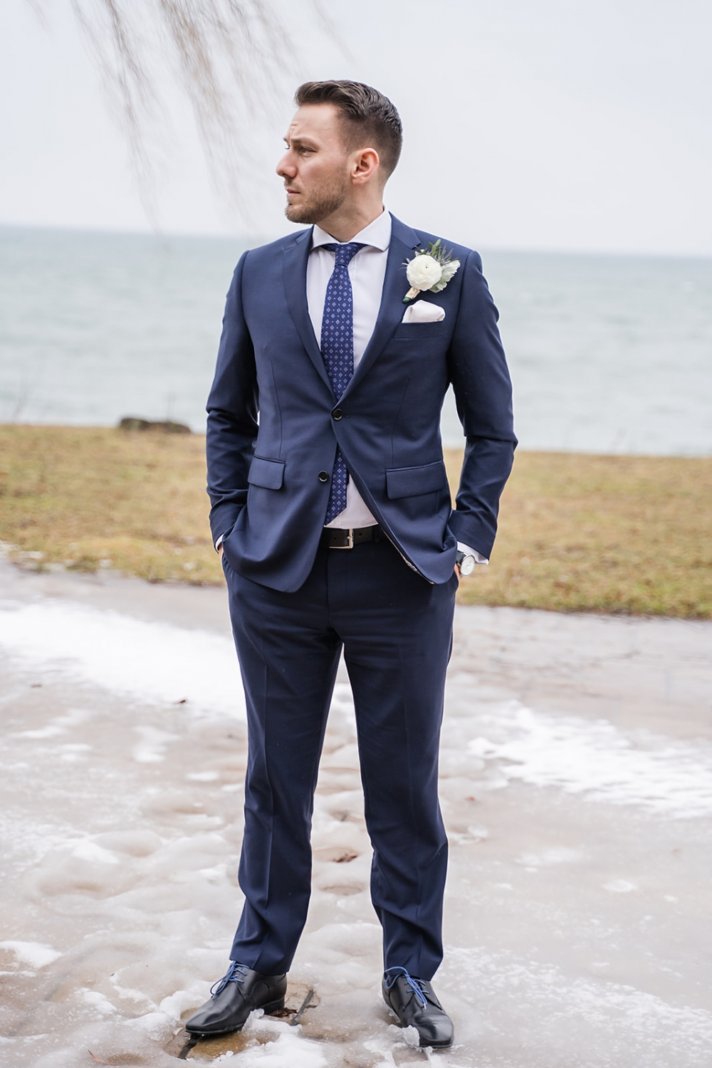 groom standing outside with his hands in his pockets as he waits for his bride