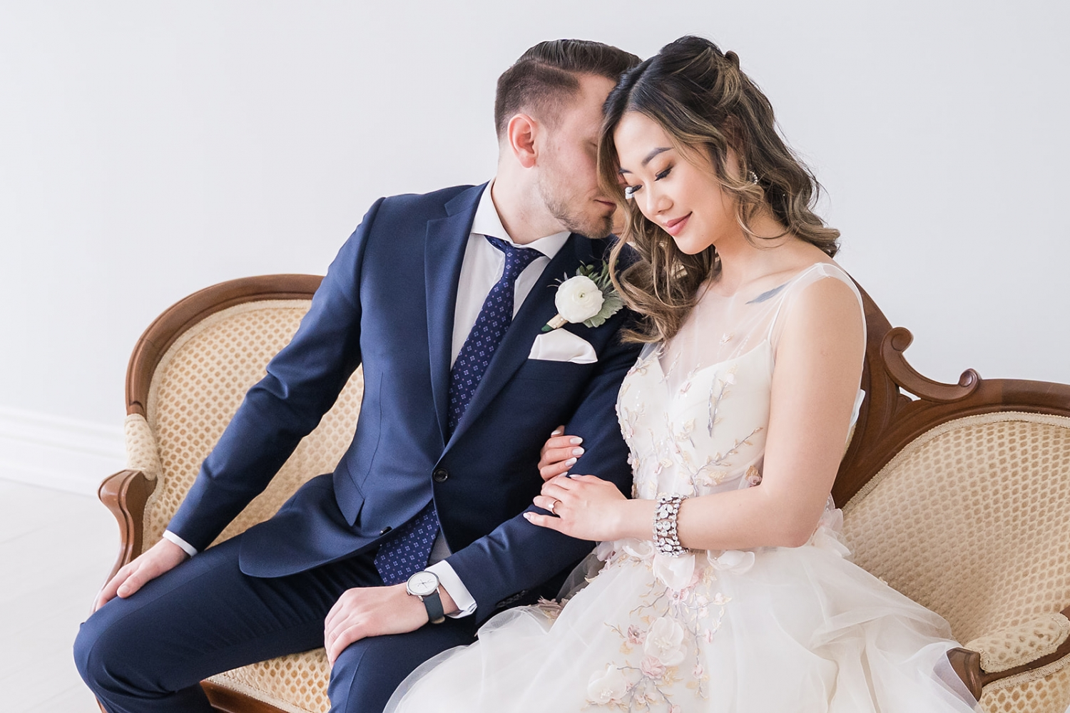 bride and groom sitting on Victorian couch