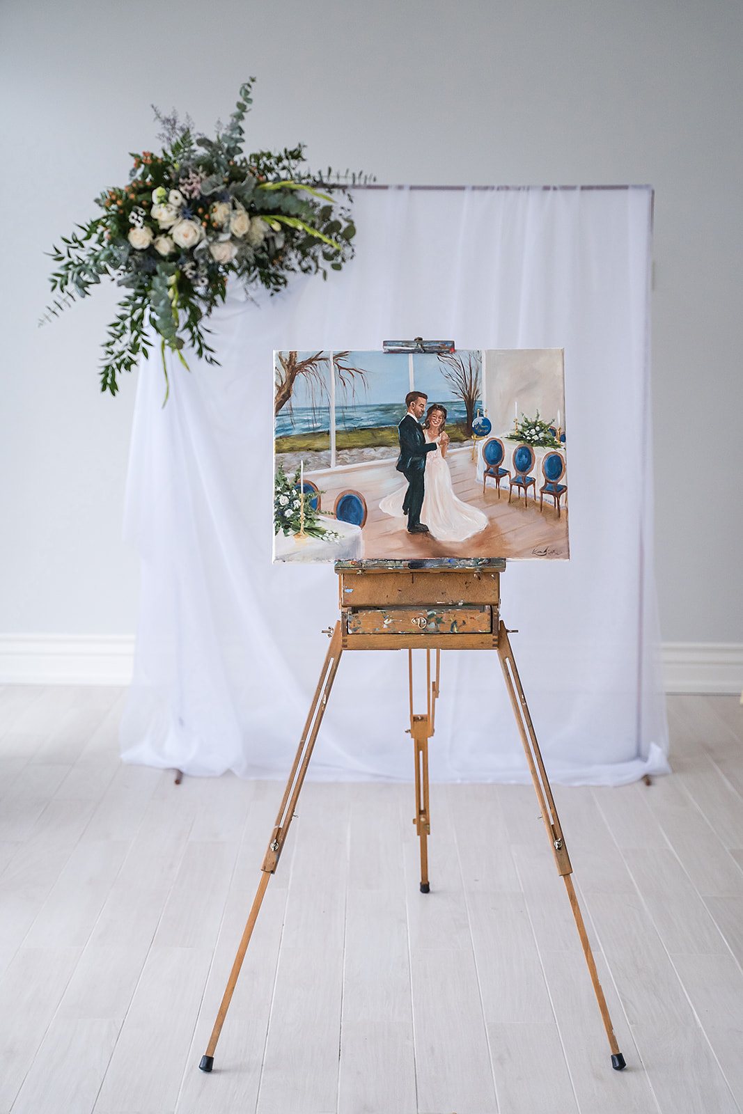 live painting of bride and groom on and easel with a floral backdrop