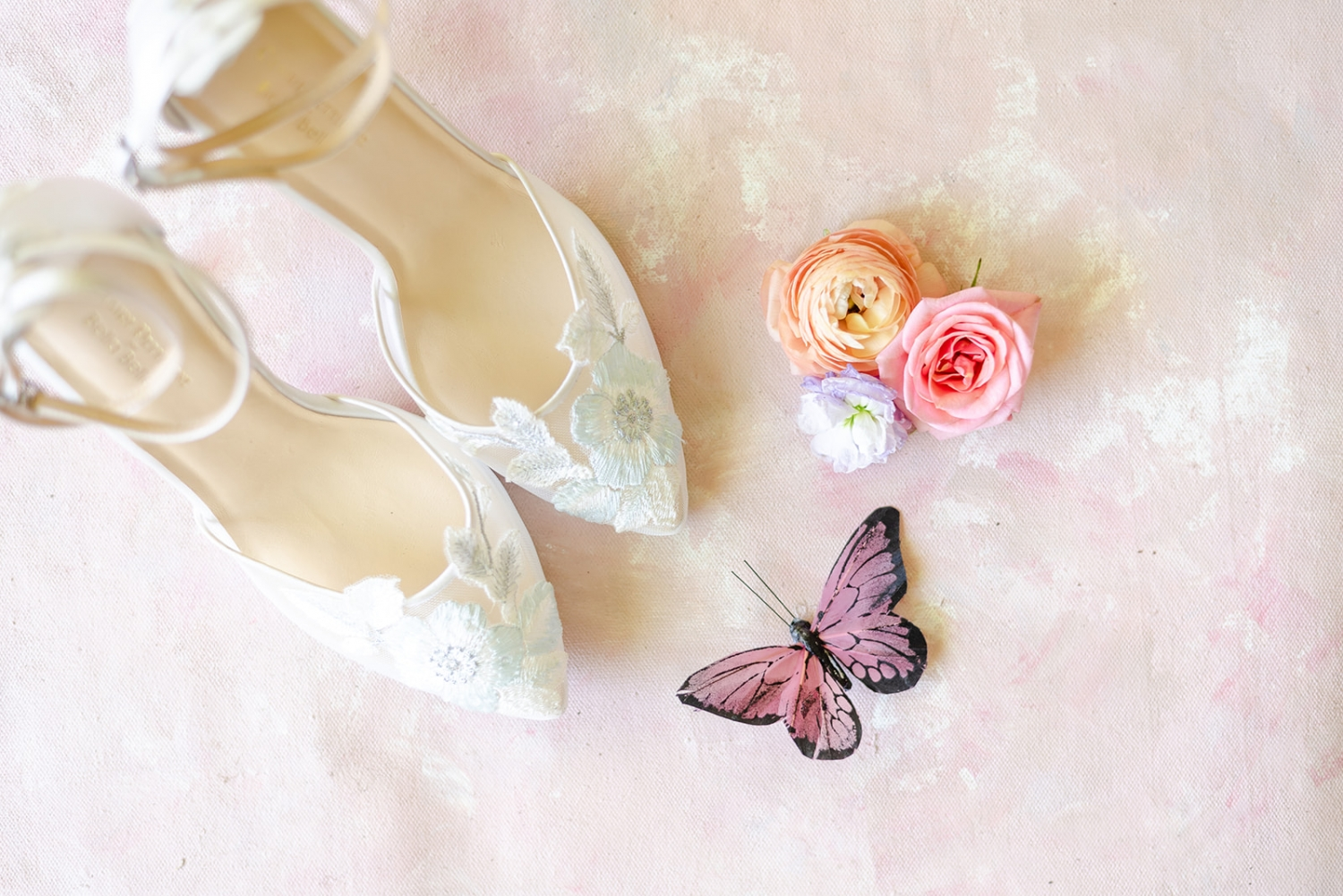 bride shoes with pink rose and peach ranunculus and a butterfly