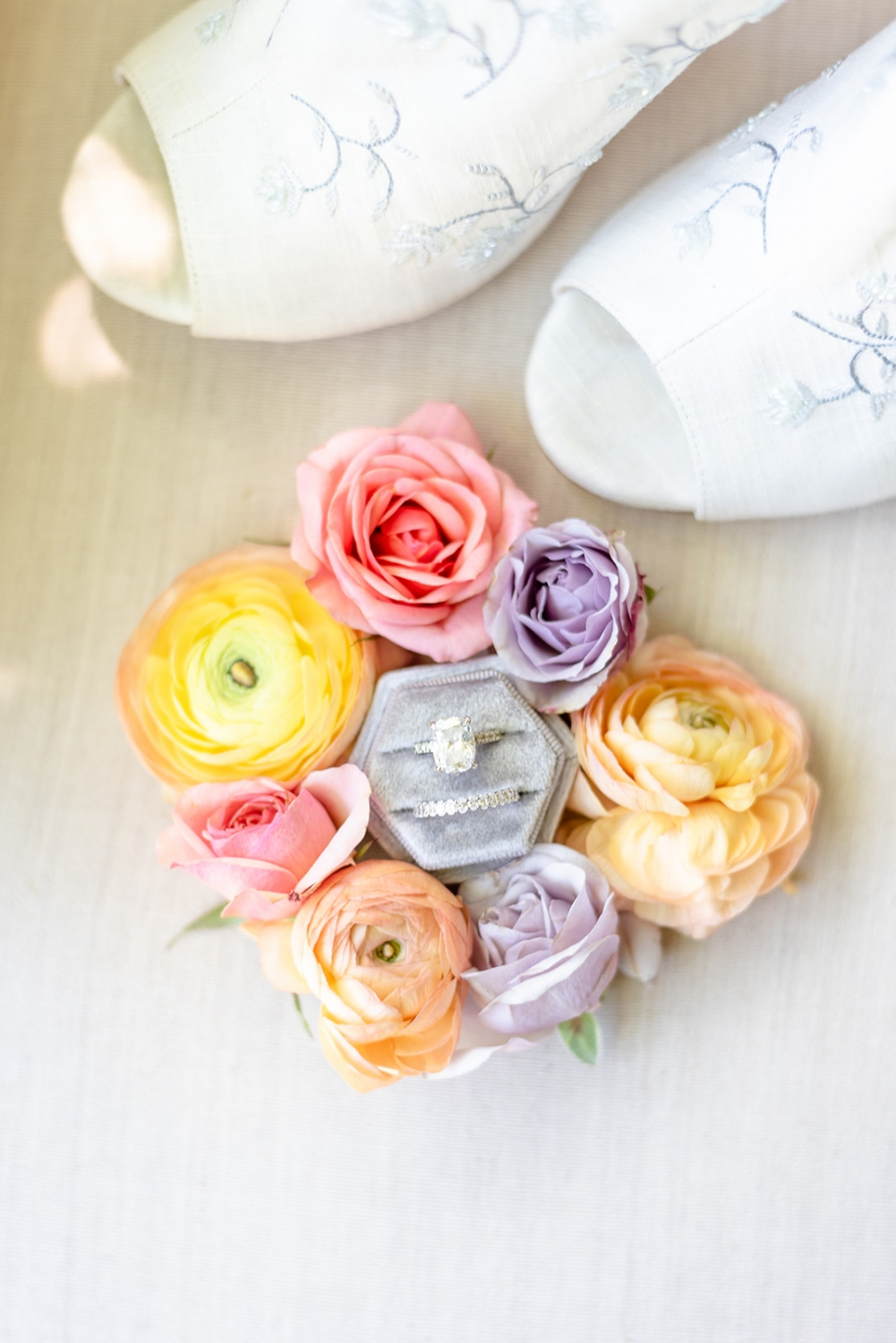 grey ring box surrounded by fresh colorful flowers