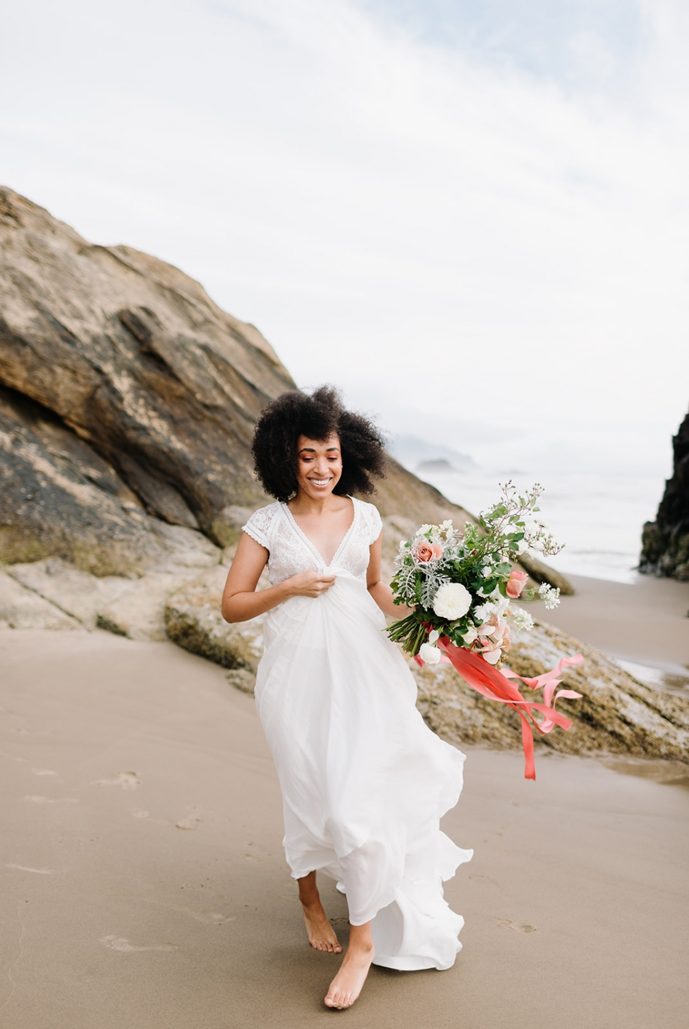 bride jogging on the beach and smiling