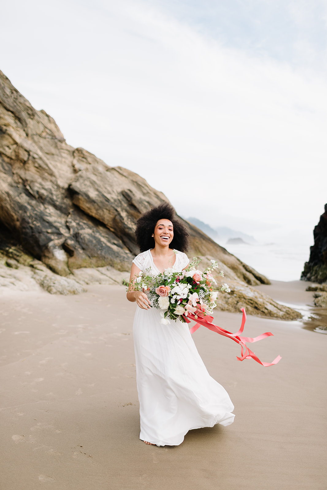 bride walking the beach holding a bouquet