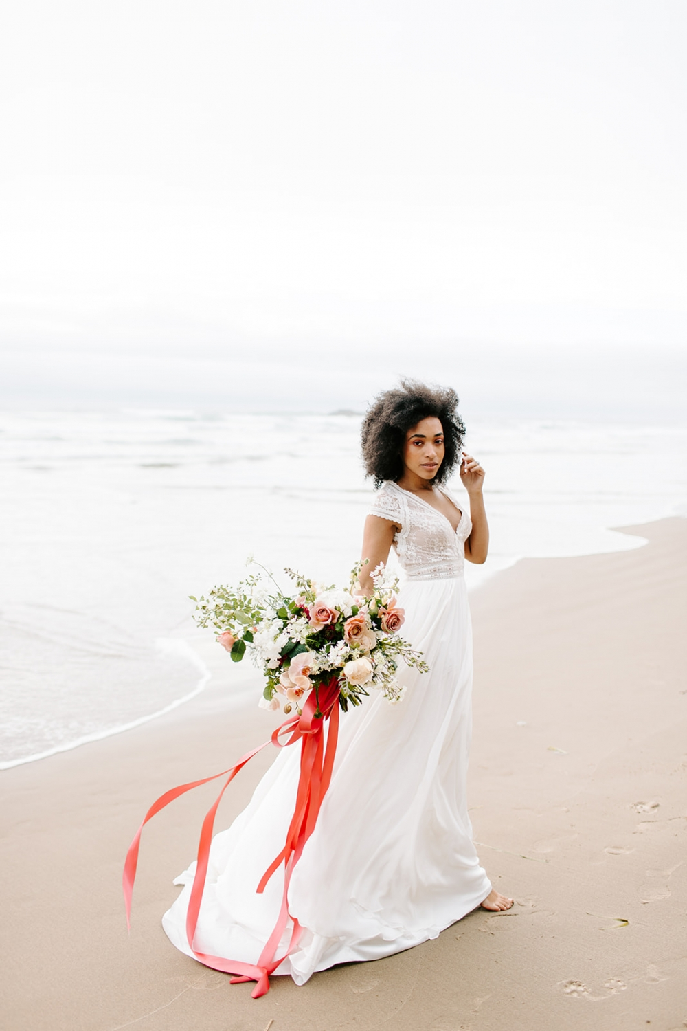 bride holding a pink ribbon bouquet on the beach