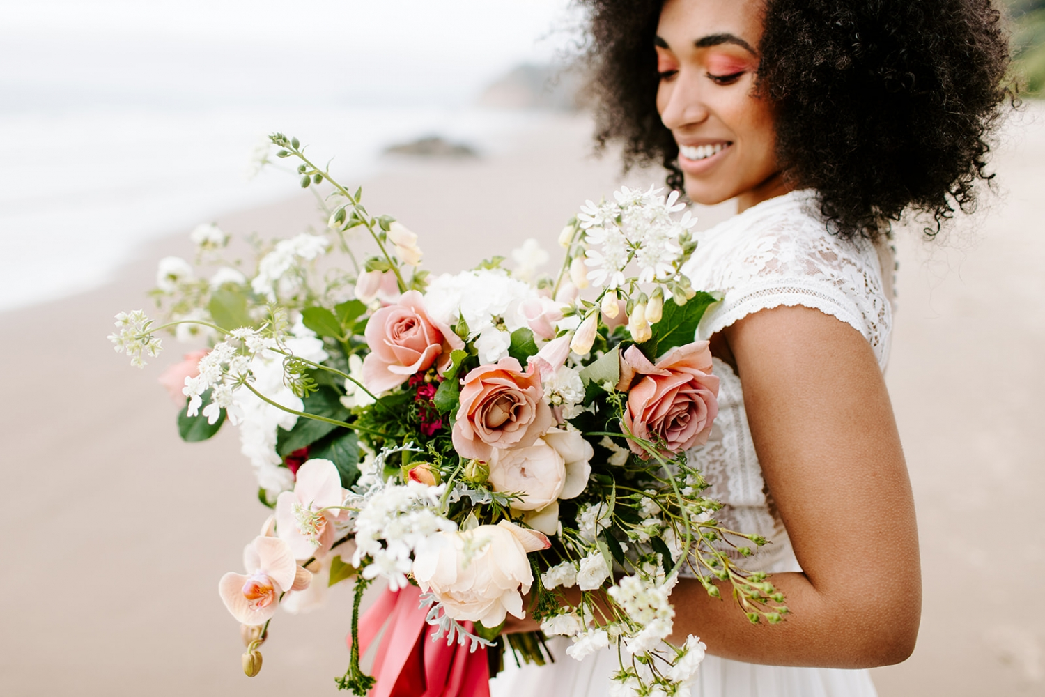 bride with coral eyeshadow holding a pink bouquet