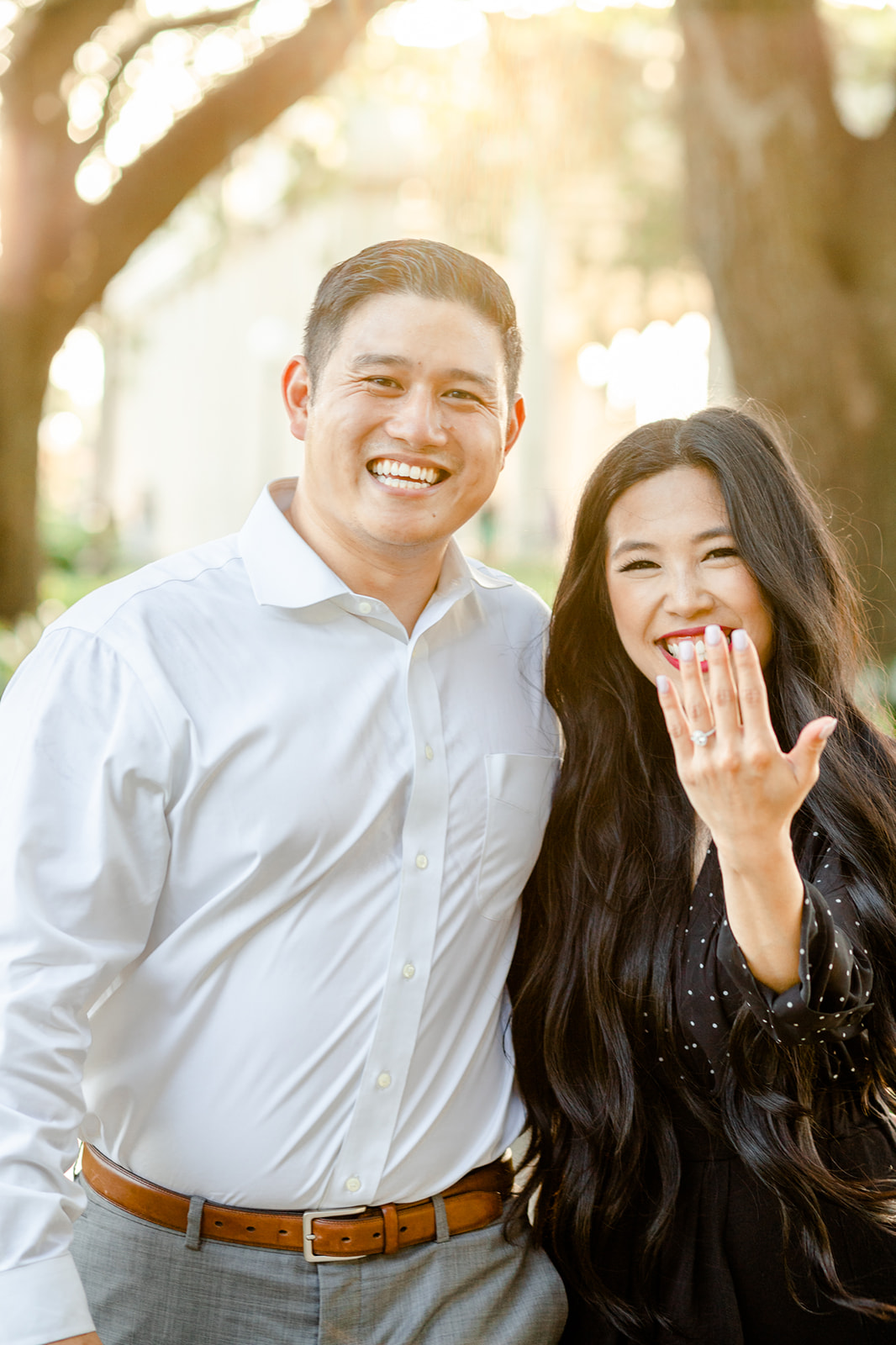 smiling couple shows off engagement ring