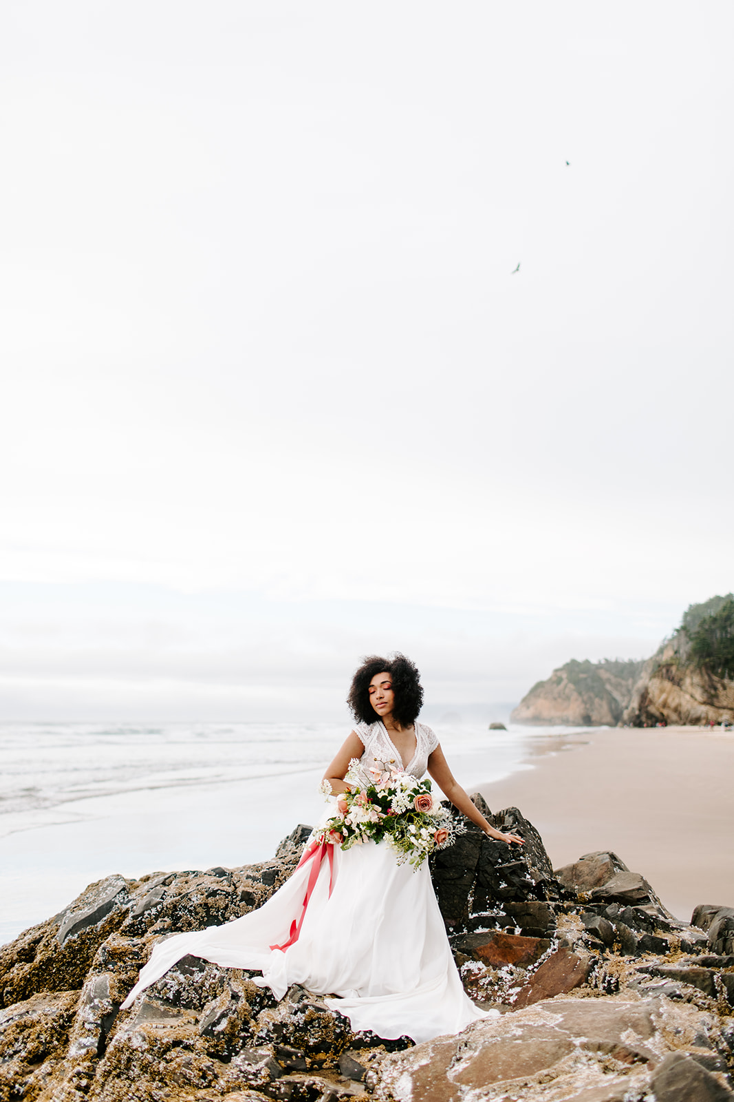 bride taking seaside portraits on rocks