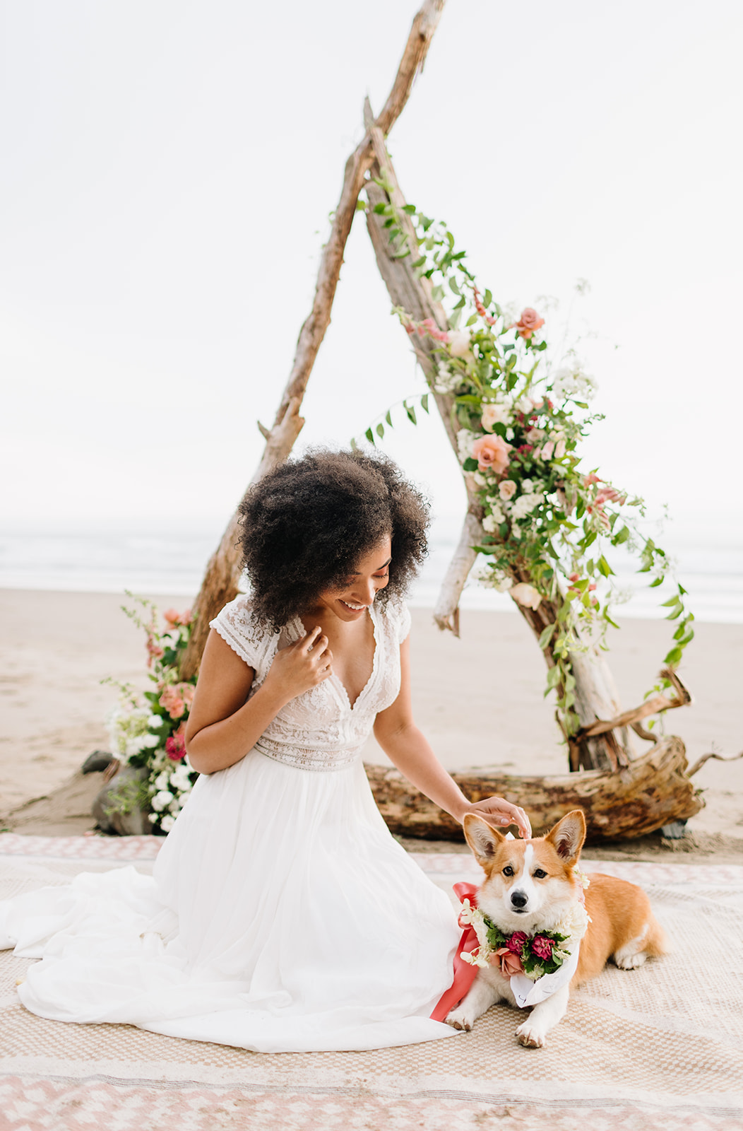 bride sitting on beach with a corgi