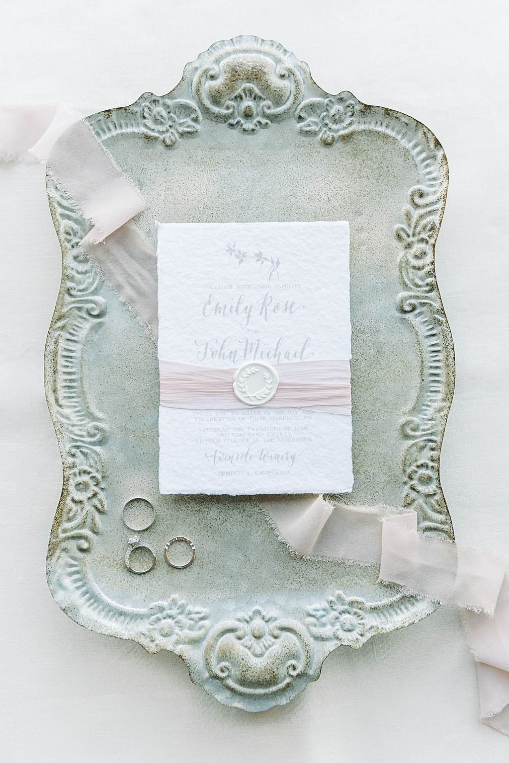 Blush pink ribbon wrapped around a wedding invitation