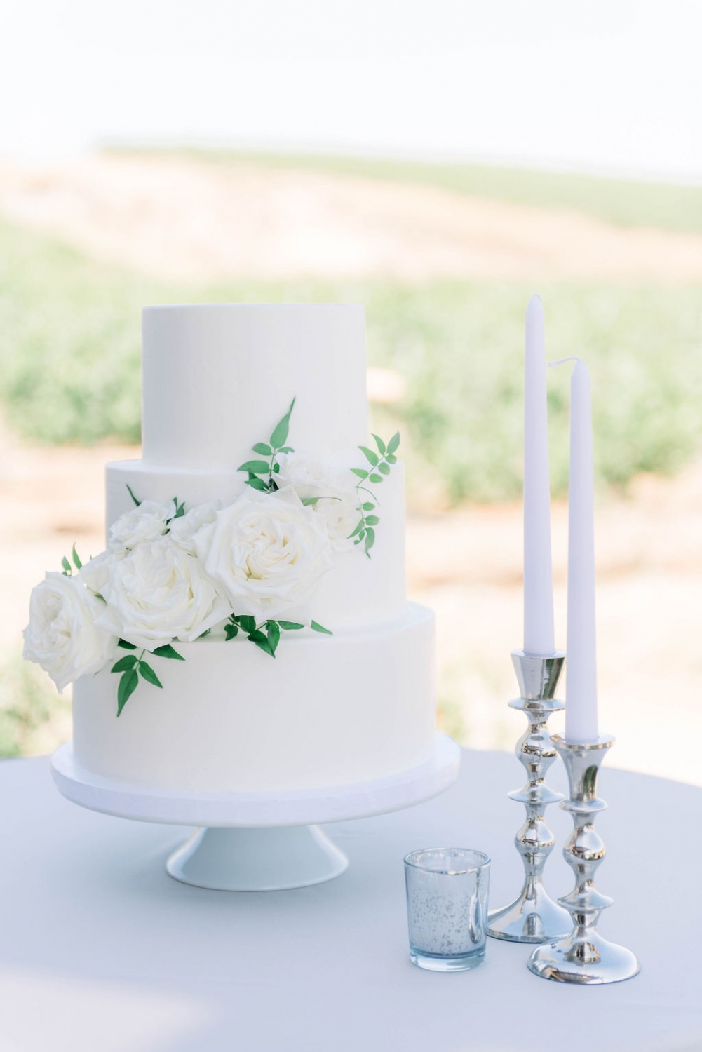 a white 3 tier cake with two tapered candlesticks in silver holders