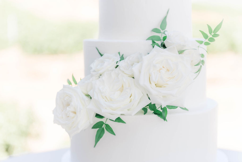 white roses on a white 3 tier wedding cake