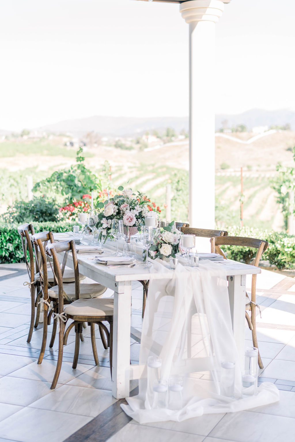 farm table setup with sheer white runner and white candles