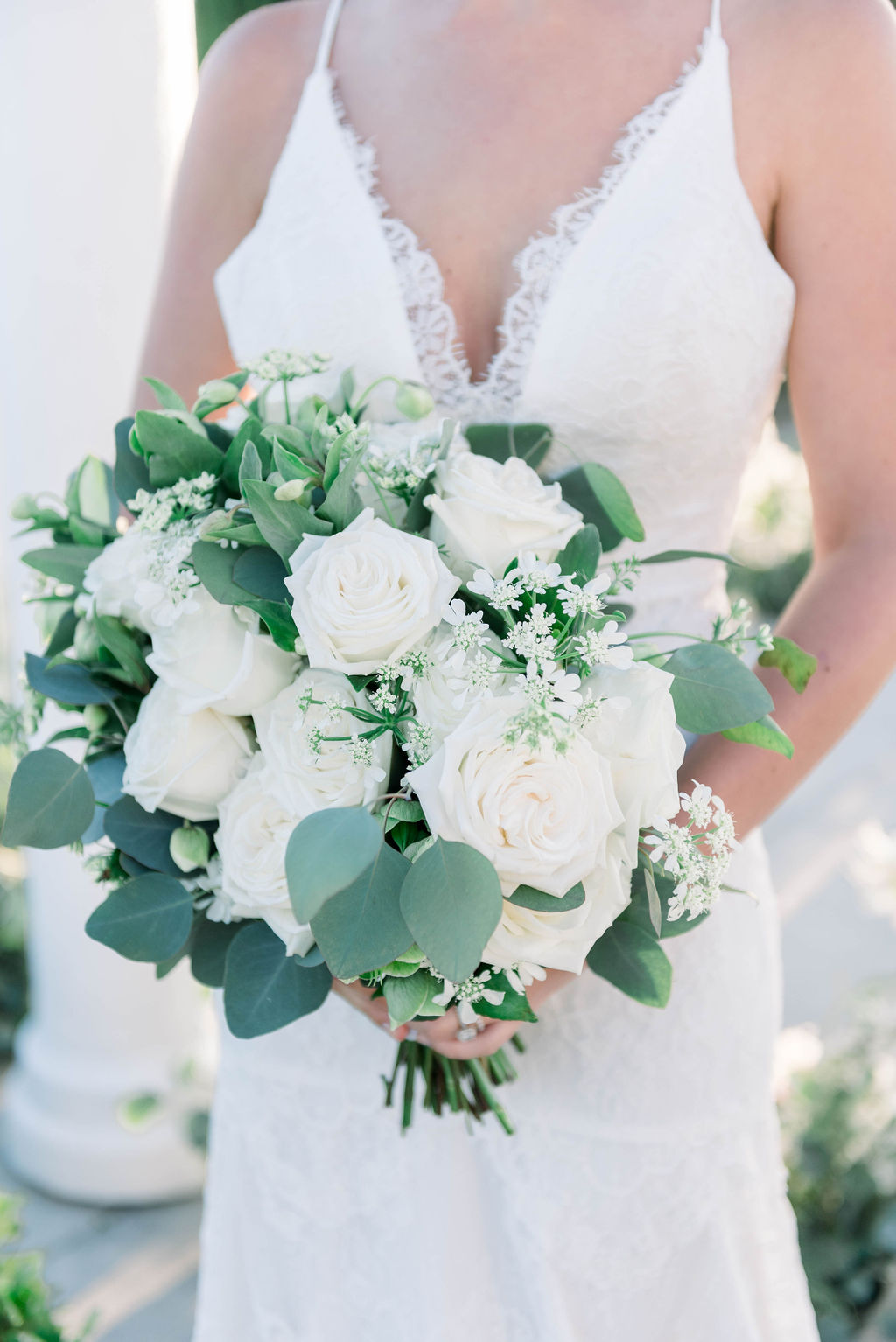 bride holding a white rose and eucalyptus bouquet