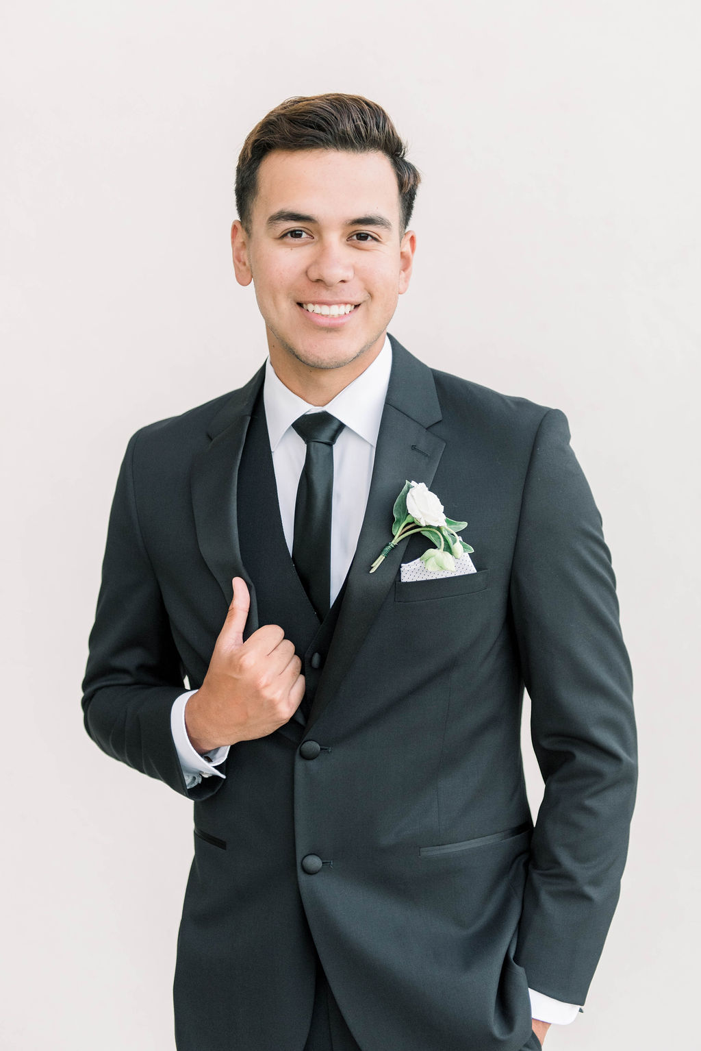 groom in a black tux and thin satin black tie