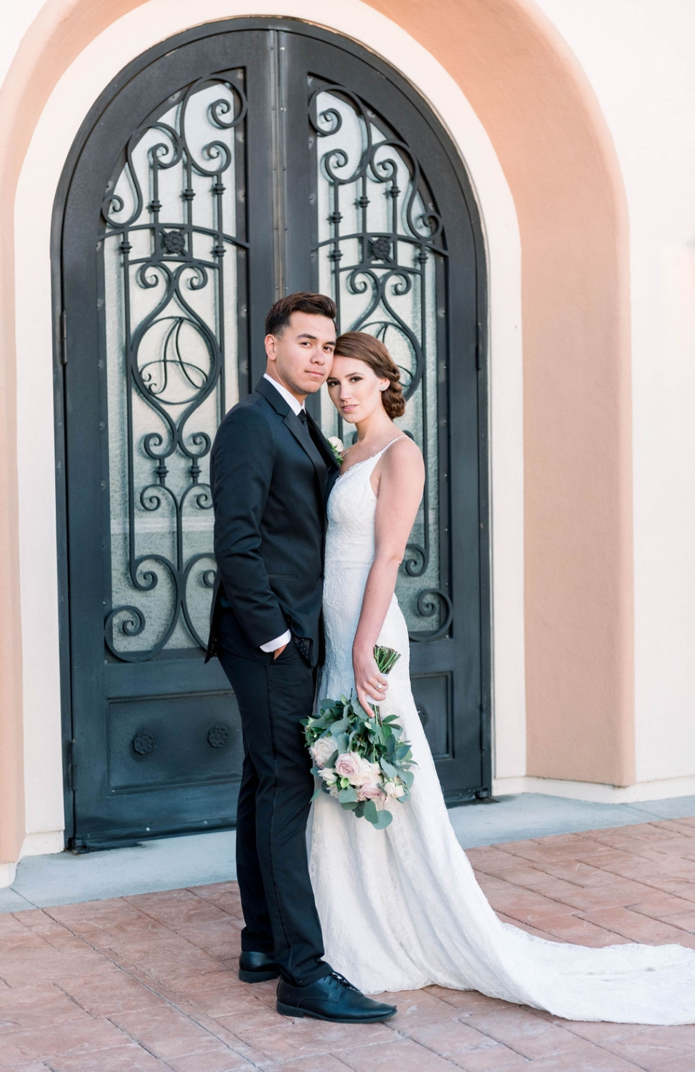 bride and groom in front gate of Avensole WInery