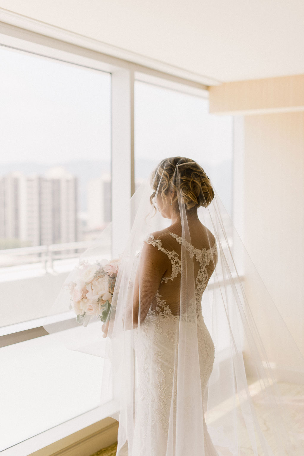 bride looking out the hotel window holding her bouquet and wearing a veil