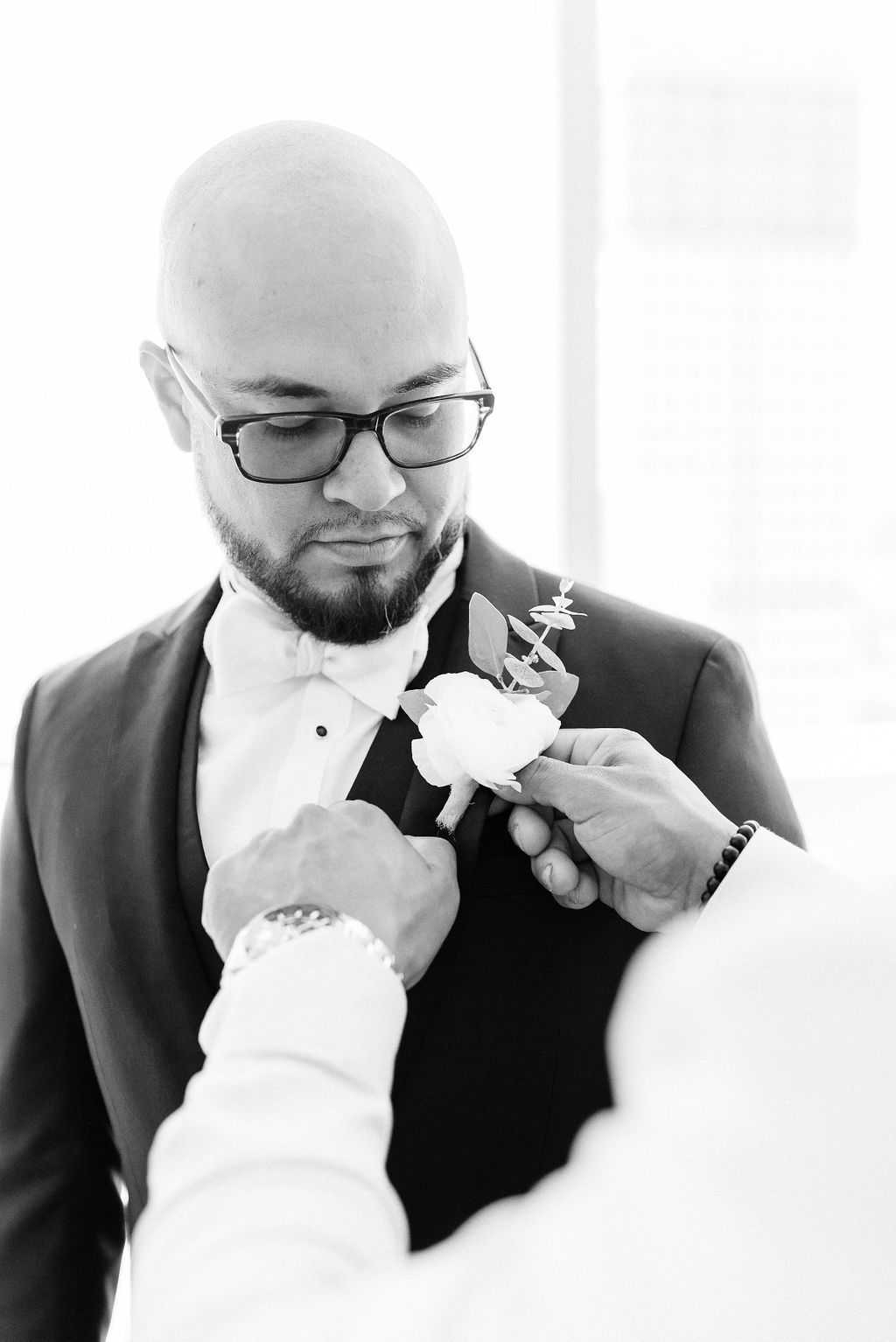 black and white photo of groom getting boutonniere pinned on