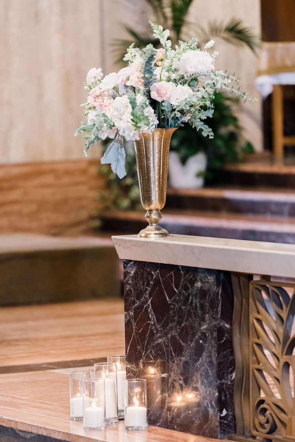 church altar with gold vase holding light colored roses for a wedding