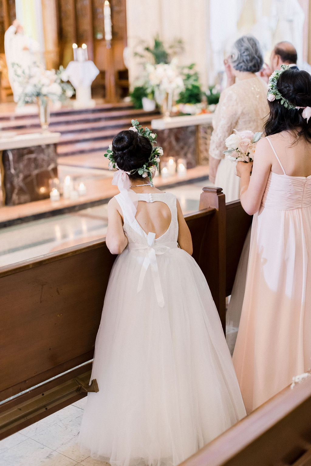 flower girl wearing an open back dress looking at the bride from the church pew
