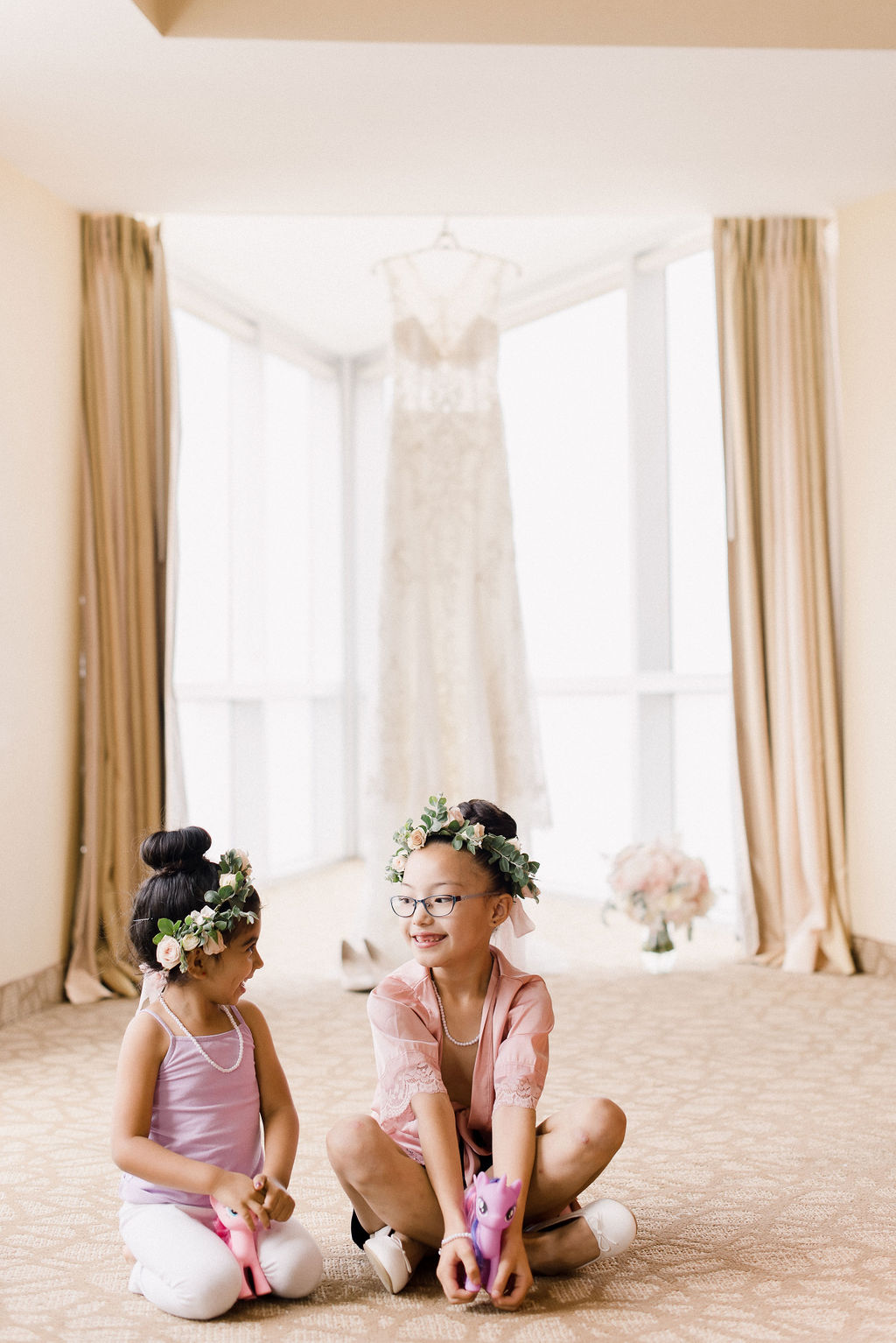 two flower girls playing as they get ready