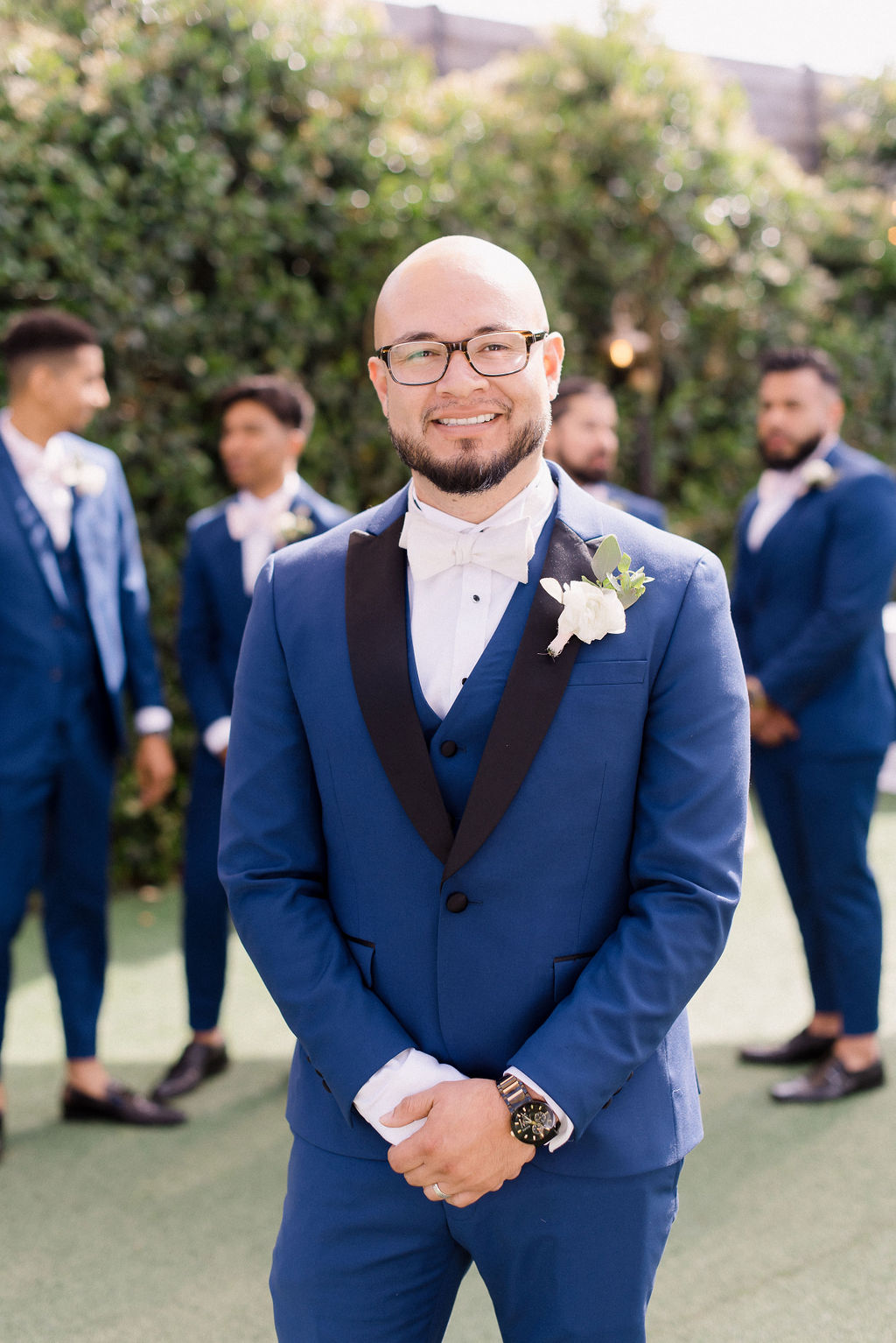 groom with a navy blue suit and black lapel
