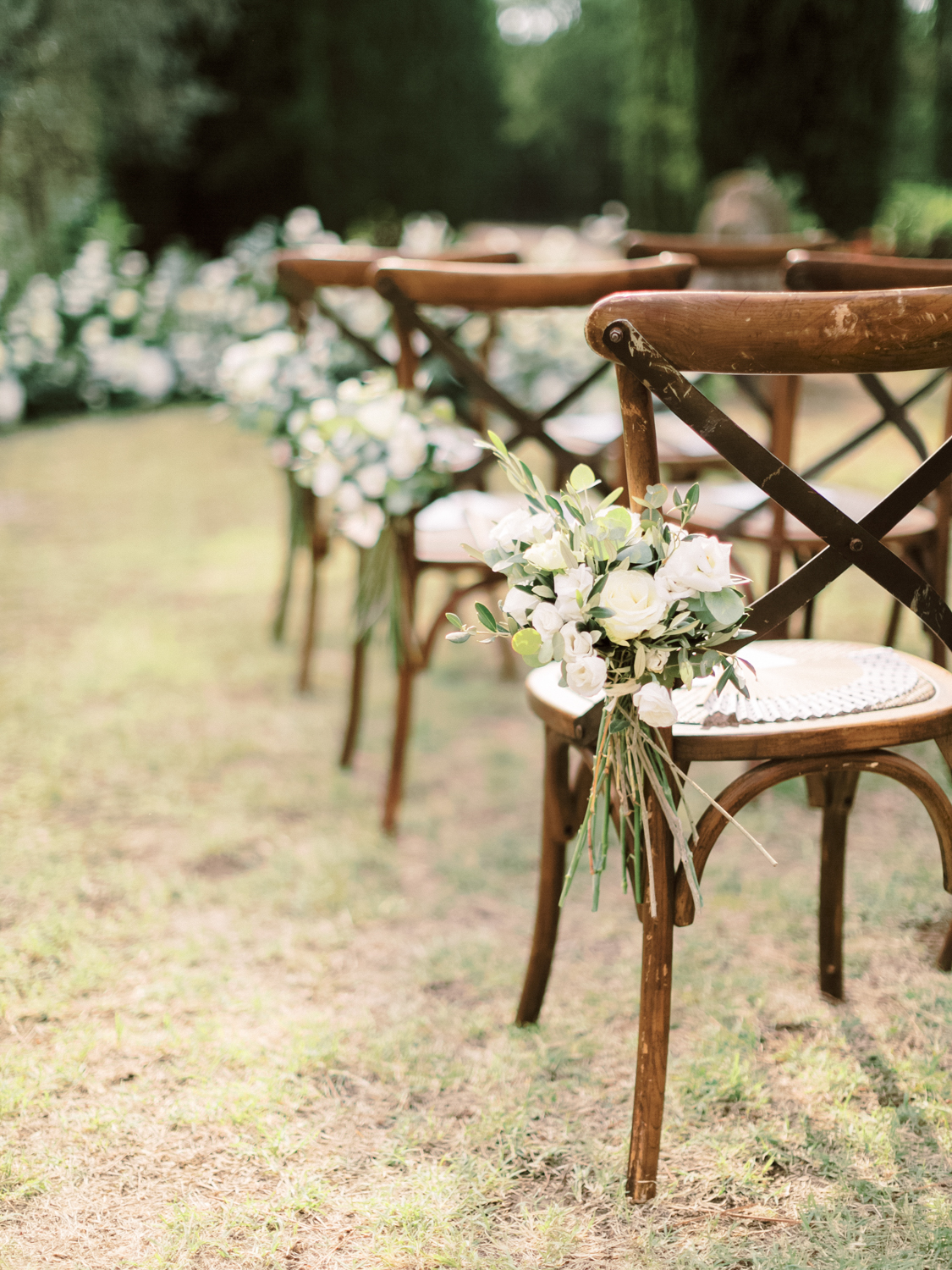 wooden wedding ceremony chairs with white floers tied to the side along the aisle