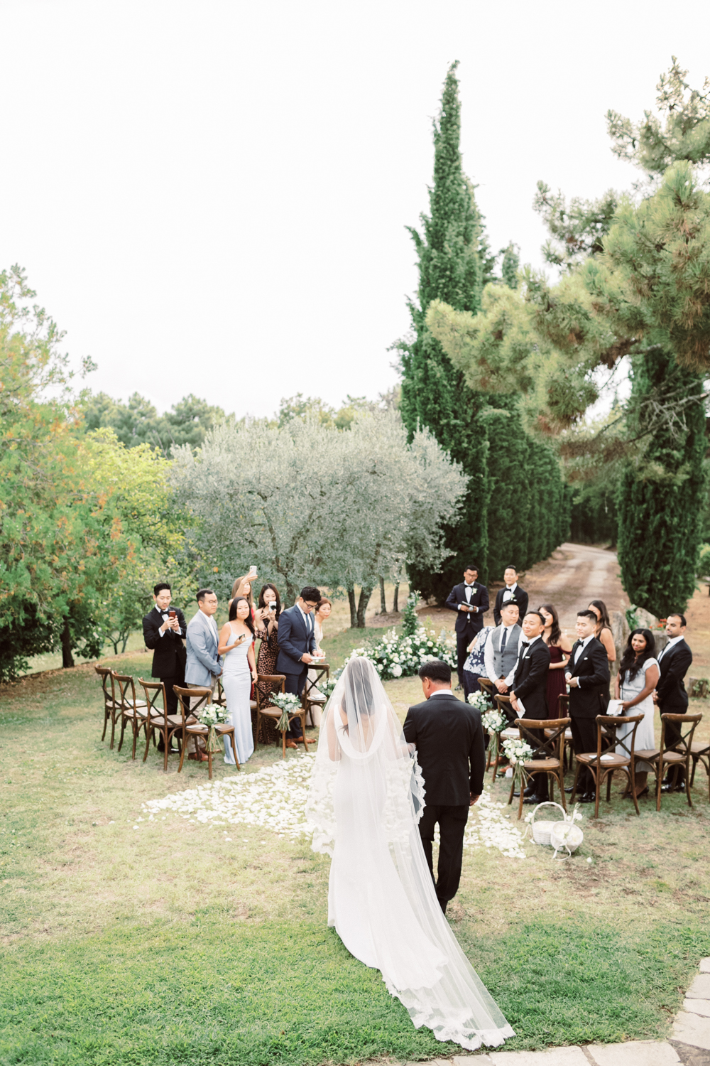 Bride is escorted by her father down the aisle outside of Tuscan villa