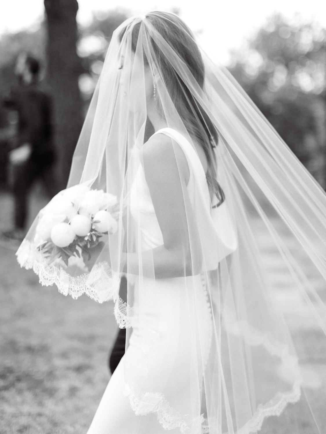 elegsnt black and white photo of bride walking down the aisle with her veil