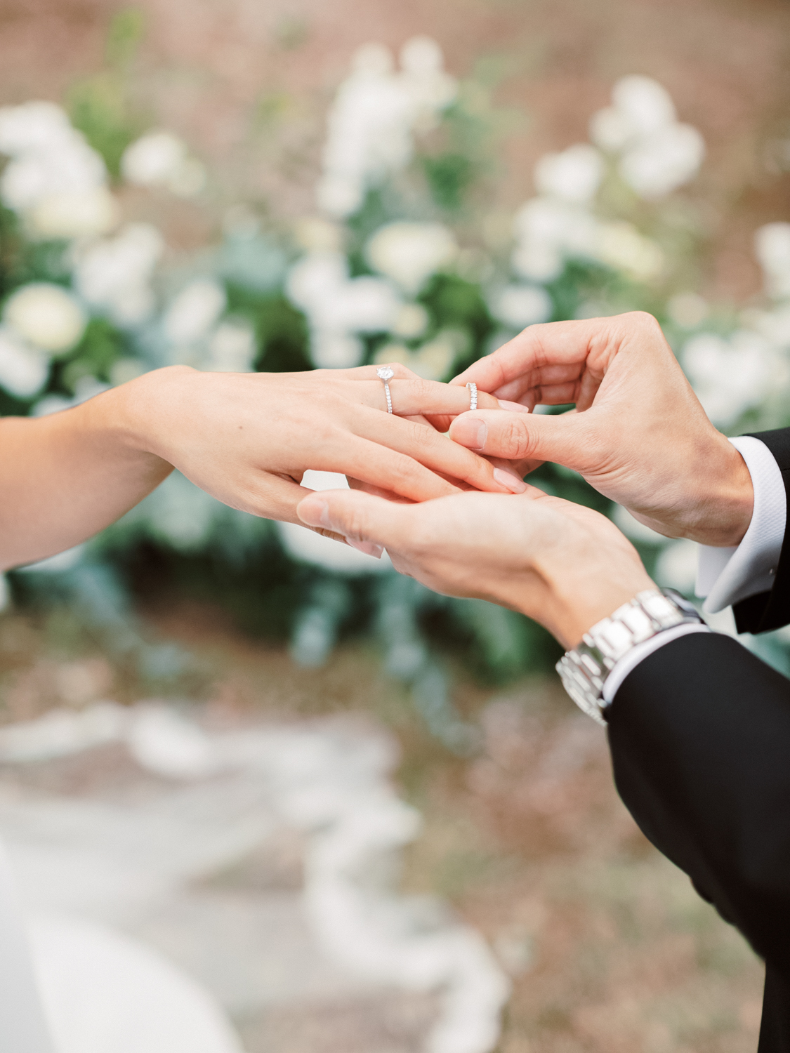 groom placing a ring on the bride's hand