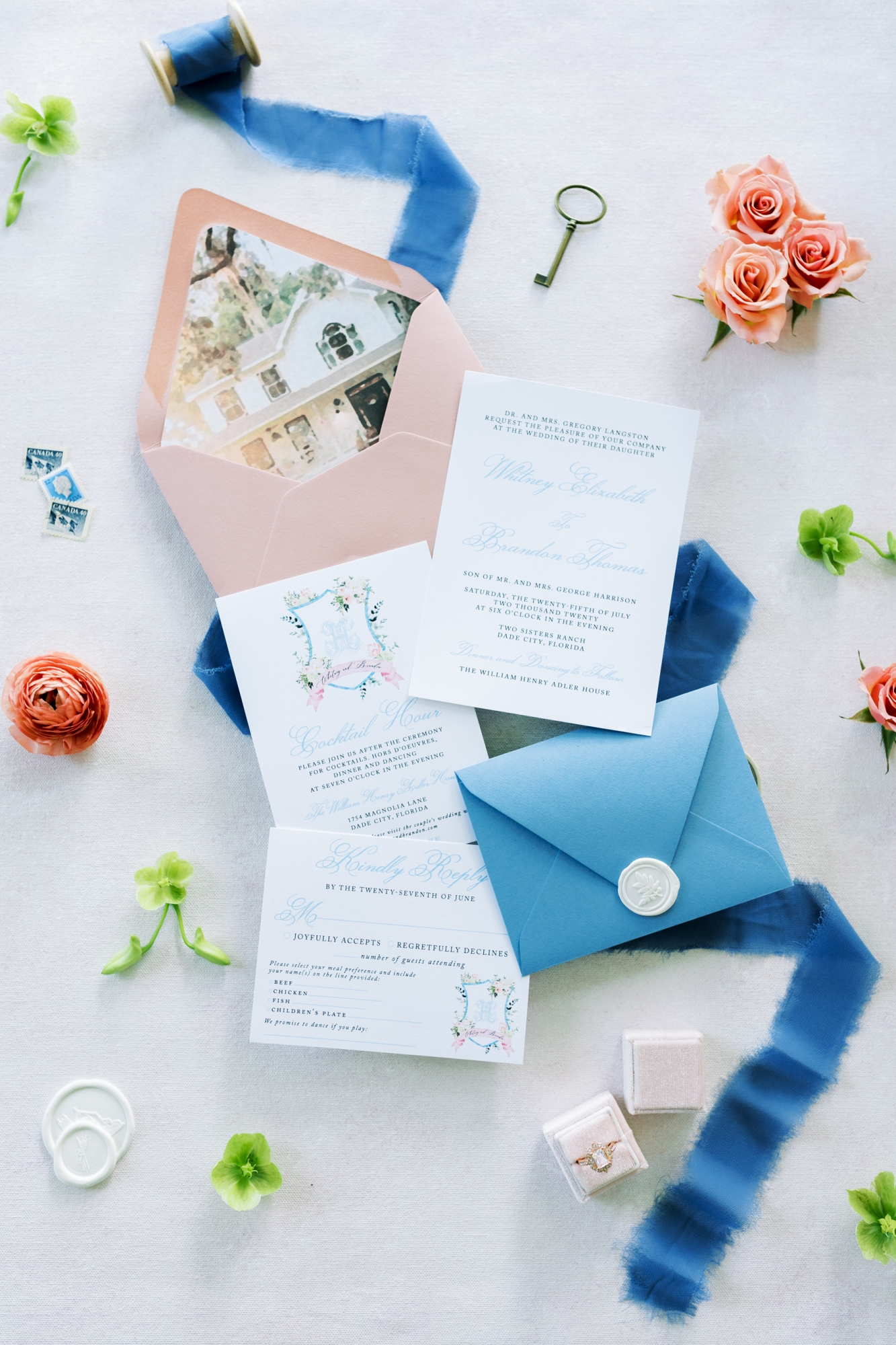 french blue invitations with a picture of the venue printed on the envelope liner