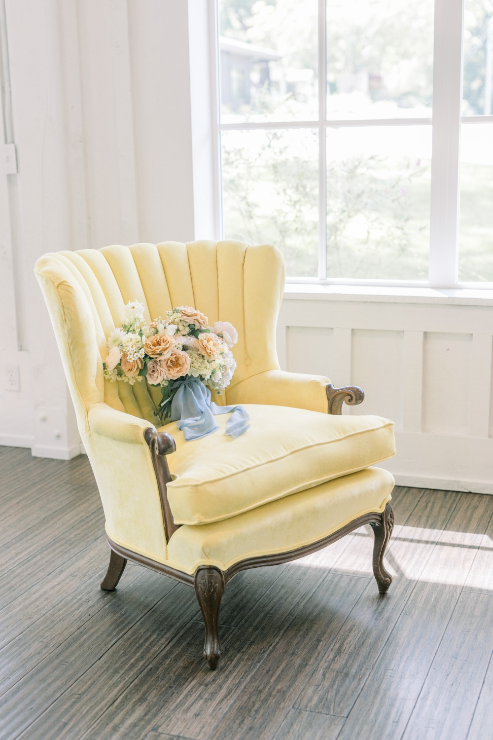 dust blue and peach bouquet on a yellow Victorian chair