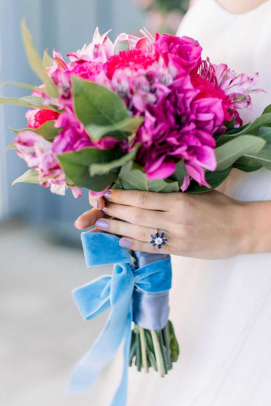 blue flower diamond ring holding pink and purple roses and flowers